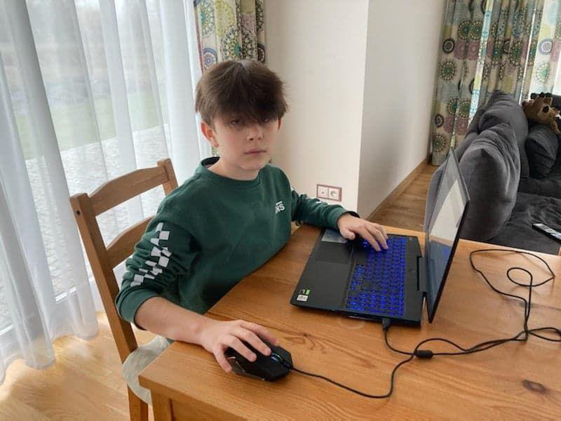 Na zdjęciu Maciej Bernacki siedzący przy biurku przy komputerze w pomieszczeniu mieszkalnym