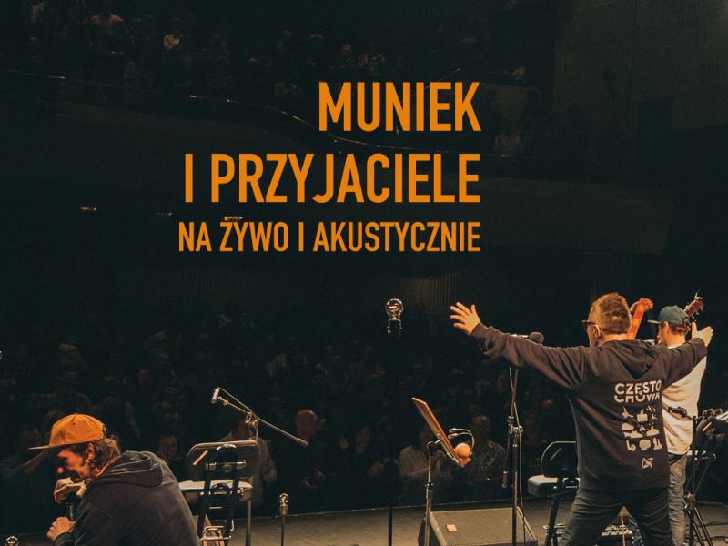 Na zdjęciu plakat projektu Muńka Staszczyka - Muniek i Przyjaciele. Na plakacie artyści na scenie, sfotografowani tyłem wśród sprzętu nagłaśniającego