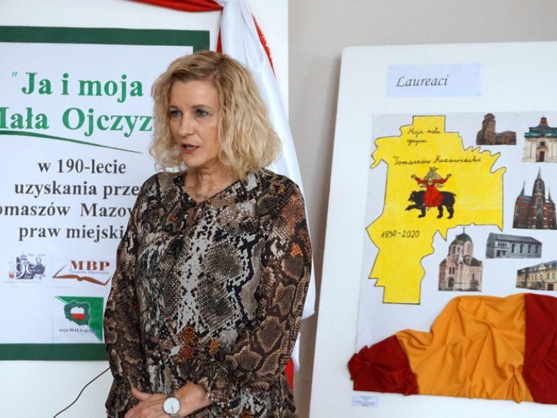 Na zdjęciu widać dyrektorkę MBP, która ogłasza werdykt konkursu literacko-plastycznego. W tle prace konkursowe na sztalugach oraz plakat z ogłoszeniem konkursu