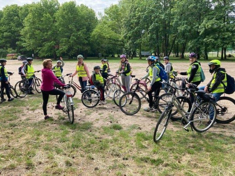 Na zdjęciu uczniowie SP nr 6, wszyscy na rowerach w kamizelkach odblaskowych i kaskach podczas wycieczki z okazji Dnia Dziecka