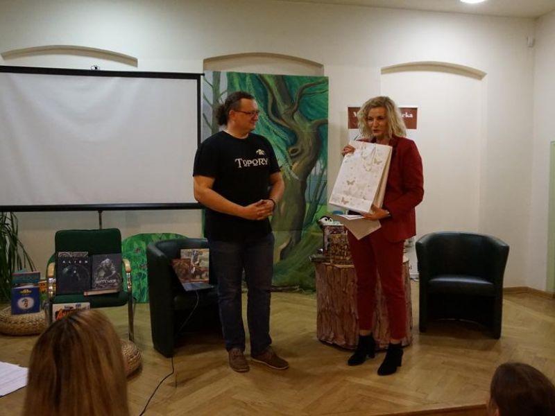 Na zdjęciu widać dyrektor biblioteki wraz z miłośnikiem gier fabularnych i literatury fantasy. Oboje stoja na scenie w sali widowiskowej MBP, dyrektorka trzyma w ręku rysunek, w tle fotele i ekran, dekoracja Nocy Bibliotek