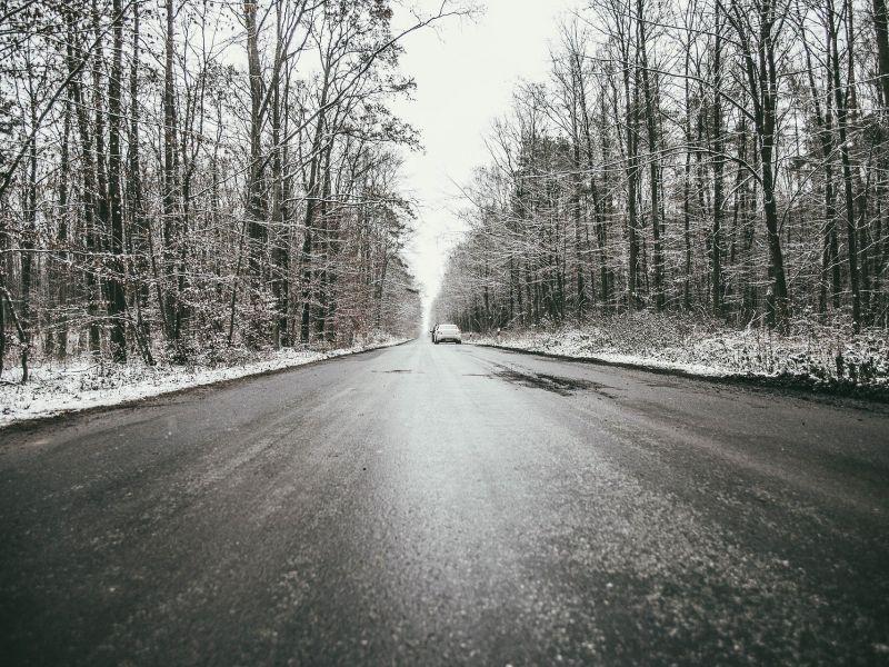 Na zdjęciu oblodzona droga asfaltowa prowadząca przez las