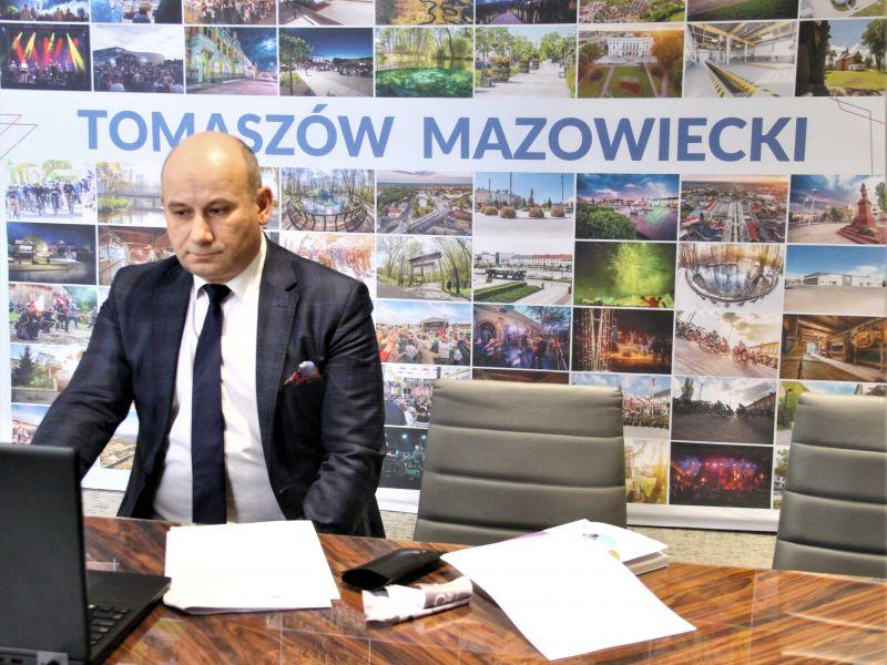 Mężczyzna w garniturze siedzi w garniturze przed komputerem zanim tło ze zdjęciami atrkacji miejskiemi i duży napis Tomaszów Mazowiecki