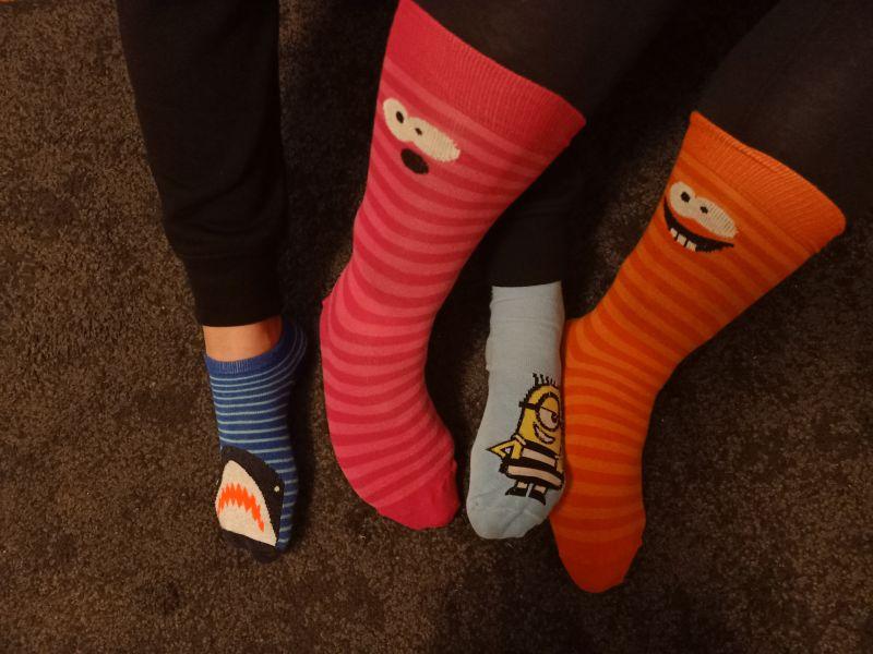 Na zdjęciu stopy dzieci w różnych skarpetkach założonych nie od pary