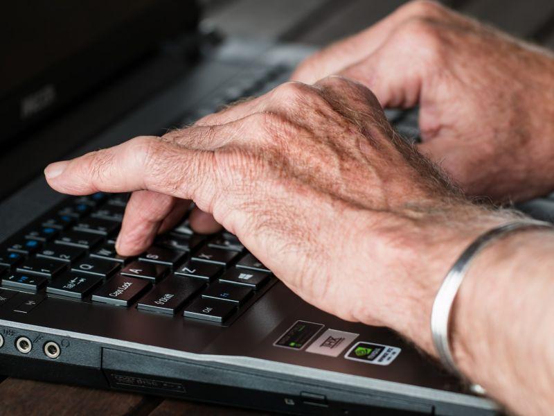 Na zdjęciu ręce seniora na klawiaturze laptopa