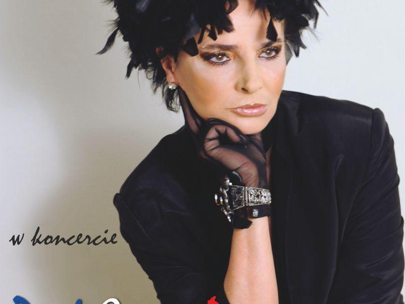 Plakat przedstawia postać wokalistki Yagi Kowalik oraz informacje na temat daty i godziny jej koncertu. Wokalistka ubrana jest w czarny kostium oraz czarny kapelusz z piór, na przegubie ręki artystyczne ozdoby ze skóry i srebra. Zdjęcie na plakacie wykadr