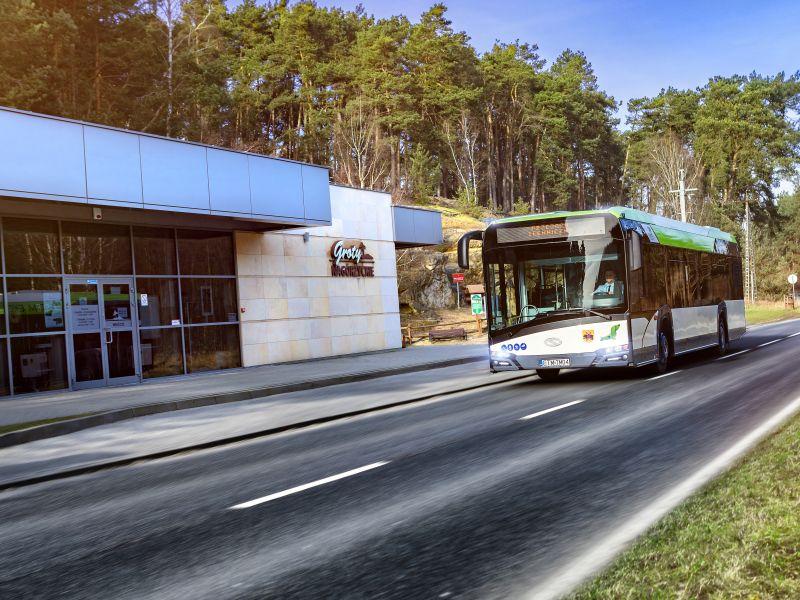 zdjęcie przedstawia autobus jadący po drodze niedleko grot nagórzyskich, widać dużo zielonych drzew budynek