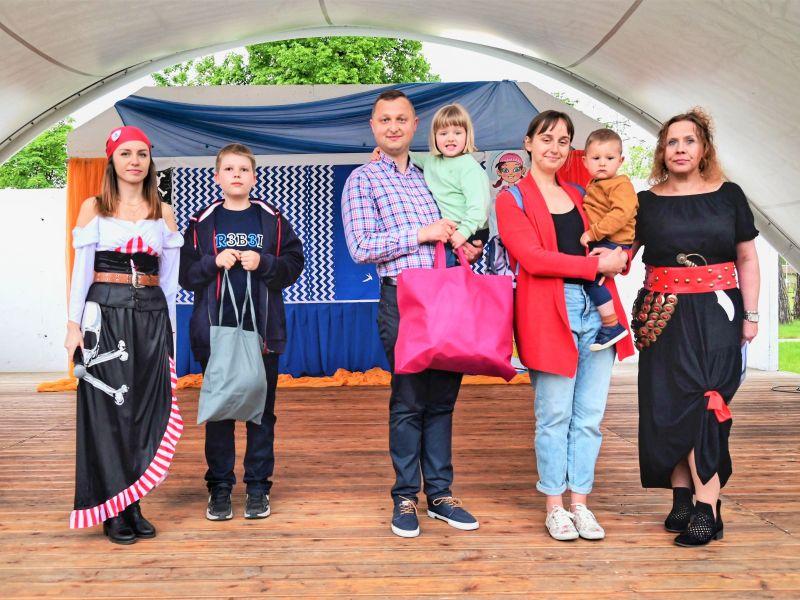 stojący na scenie ludzie i trójka małych dzieci oraz dwie kobiety przebrane za piratki