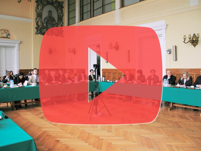 zdjęcie rady miejskiej w sali plenarnej, na nim grafika - duży półprzezroczysty kwadrat w wciętym po środku trójkątem - tzw. znaczek