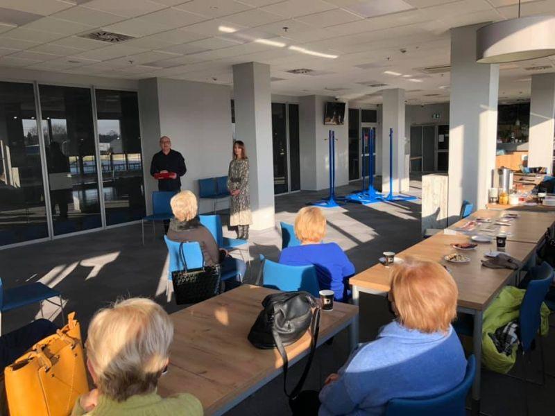 Na zdjęciu widać seniorów na sali konferencyjnej Areny Lodowej podczas prelekcji. Seniorzy siedzą na krzesłach, prelegenci (kobieta i mężczyzna) prowadzą pogadankęprowadzą spotkanie