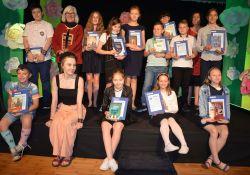 Na zdjęciu laureaci Małego Konkursu Recytatorskiego w kategorii klas 4-6. Zdjęcie grupowe, dzieci  siedzą na scenie, prezentują nagrody oraz dyplomy
