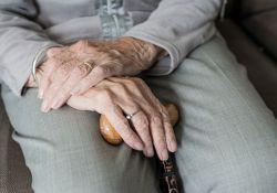 Na zdjeciu zbliżenie dłoni osoby starszej (seniora). W dłoniach senior trzyma drewnianą laskę
