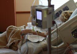 Zdjęcie ilustracyjne, kobieta leży w łóżku szpitalnym, obok niej stoją medyczne urządzenia
